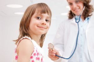 Female doctor examining happy child