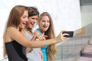 Group of three teenager girls amazed watching the smart phone