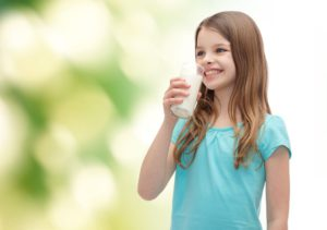 health and beauty concept - smiling little girl drinking milk out of glass